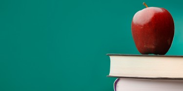 Apple, textbook and a blackboard